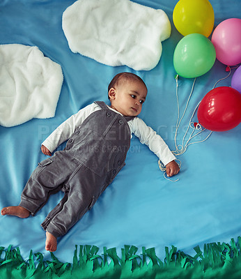 Buy stock photo Concept shot of an adorable baby boy flying through the sky holding a bunch of balloons