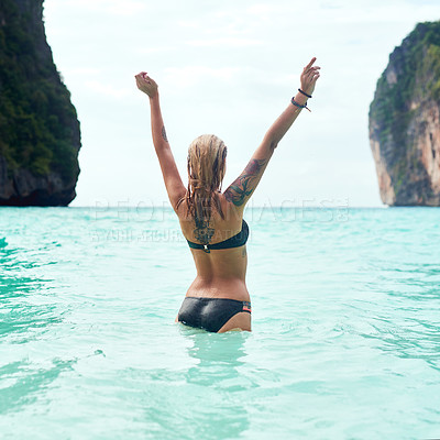 Buy stock photo Rear view shot of a beautiful young woman standing in the ocean