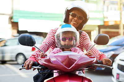 Buy stock photo Portrait of a mother and her little daughter sitting on a scooter outside