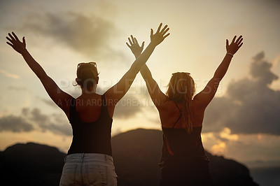Buy stock photo Rearview shot of two young friends with their arms raised silhouetted against a sunset