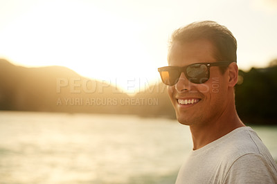 Buy stock photo Portrait of a handsome young man standing on the beach at sunset