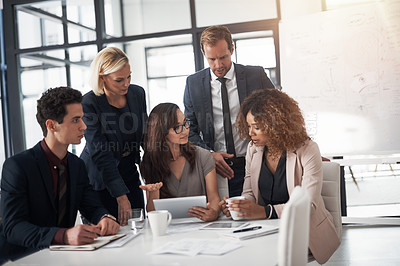 Buy stock photo Cropped shot of a group of businesspeople using a digital tablet during a meeting in an office