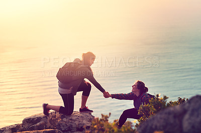 Buy stock photo Shot of a young woman helping her friend up a mountain