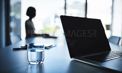 Buy stock photo Cropped shot of a laptop and a glass of water on a boardroom table with a businesswoman in the background