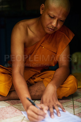Buy stock photo Shot of a buddhist monk filling in a form while sitting in the doorway of his home