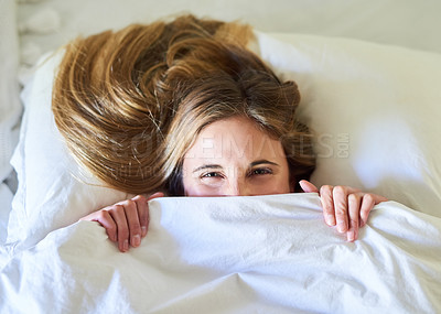 Buy stock photo Portrait of a playful young woman hiding under the covers in her bed