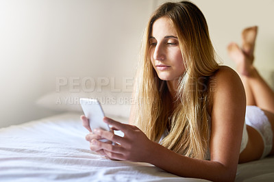 Buy stock photo Shot of a beautiful young woman using her smartphone while relaxing on her bed