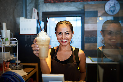 Buy stock photo Portrait of a young barista holding up a chilled coffee beverage in a coffee shop