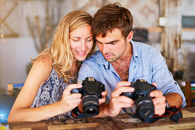 Buy stock photo Shot of a young couple looking at pictures on their camera while on holiday in Thailand
