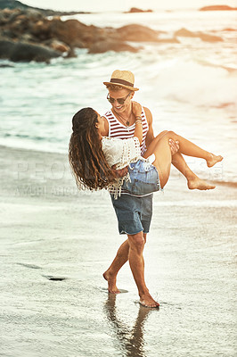 Buy stock photo Full length shot of an affectionate young couple enjoying their time on the beach
