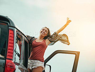 Buy stock photo Portrait of a young woman leaning out a car with her arms outstretched while on a roadtrip