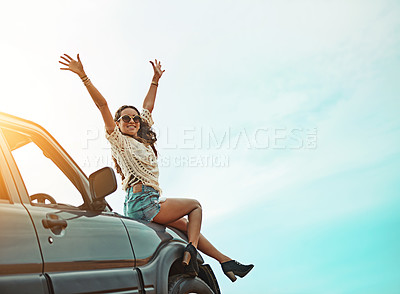Buy stock photo Portrait of a young woman sitting on a car with her arms outstretched while on a roadtrip