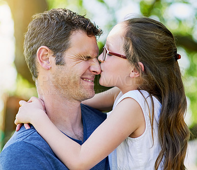 Buy stock photo Cropped shot of a little girl giving her father a kiss outside