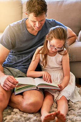 Buy stock photo Cropped shot of a father and his little daughter reading a book together at home