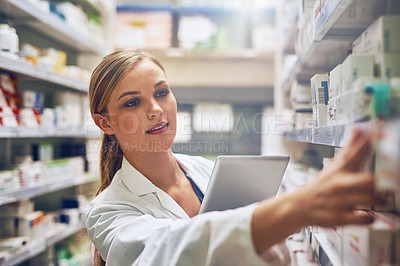 Buy stock photo Shot of a pharmacist using her digital tablet while working in a isle