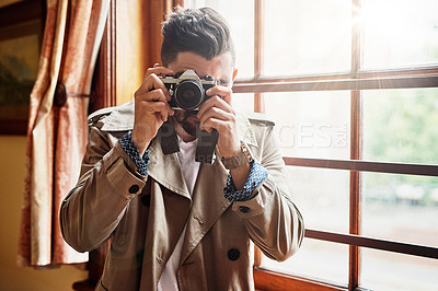 Buy stock photo Shot of a handsome young man  standing by a window at home using a camera