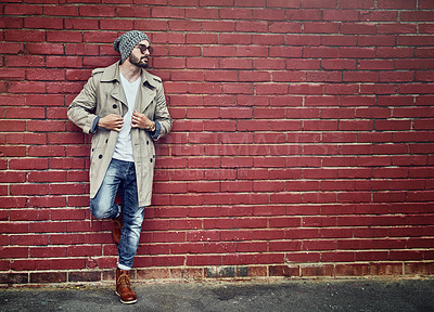 Buy stock photo Shot of a fashionable young man wearing urban wear and posing against a brick wall