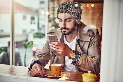 Buy stock photo Shot of a stylish young man reading a text message while sitting at a counter in a cafe