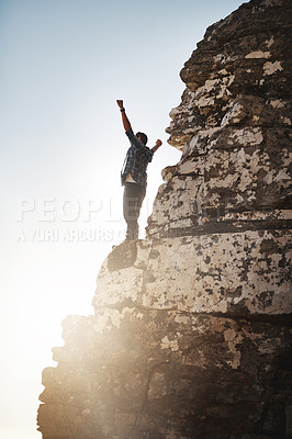 Buy stock photo Shot of a young man standing on a mountain cliff with his arms raised