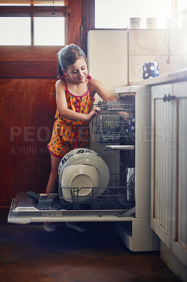 Buy stock photo Shot of a little girl using a dishwashing machine at home