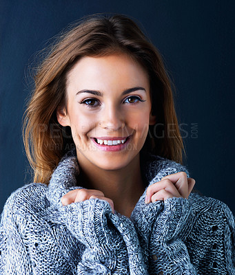 Buy stock photo Studio portrait of a cute teenage girl in a sweater posing against a dark background