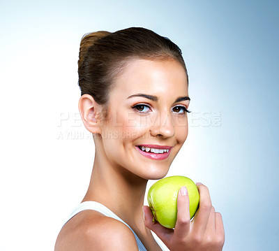 Buy stock photo Portrait of a health-conscious young woman posing with an apple in studio