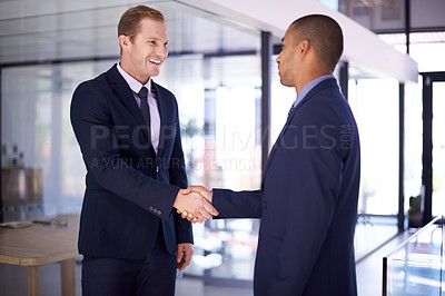 Buy stock photo Cropped shot of two businessmen shaking hands in an office