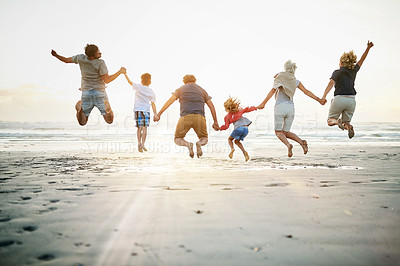 Buy stock photo Rearview shot of a happy multi-generational family jumping on the beach