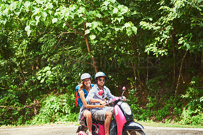 Buy stock photo Shot of a happy young couple exploring an exotic destination by scooter