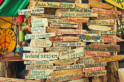 Buy stock photo Shot of a sign in a bar showing the distance to various travel destinations