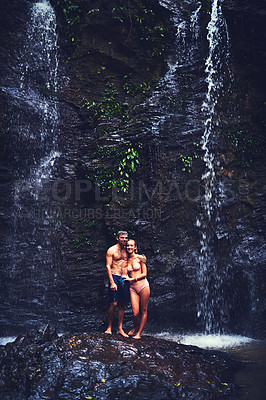 Buy stock photo Portrait of a happy young couple standing under a waterfall in the jungle