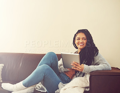 Buy stock photo Shot of a young woman relaxing at home with her digital tablet
