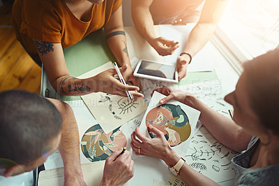 Buy stock photo High angle shot of a group of young designers working around a drafting table