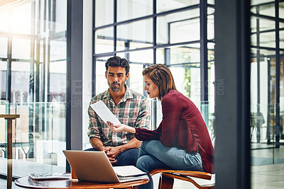 Buy stock photo Shot of two young designers working together in their office