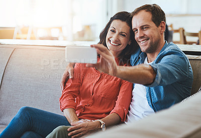 Buy stock photo Cropped of an affectionate couple taking selfies on the sofa at home