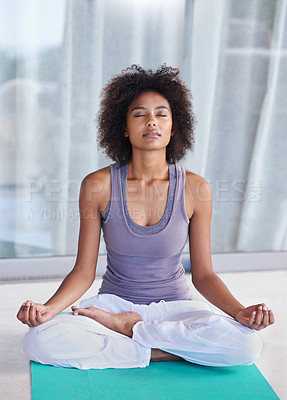 Buy stock photo Shot of an attractive young woman meditating on an exercise mat