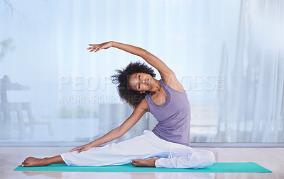 Buy stock photo Shot of an attractive young woman stretching on an exercise mat