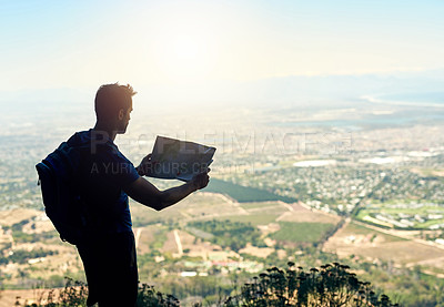 Buy stock photo Rear view shot of a young man reading a map while standing at the top of a mountain