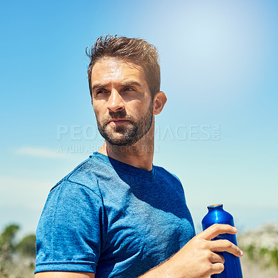 Buy stock photo Cropped shot of a young man taking a break while out for a run