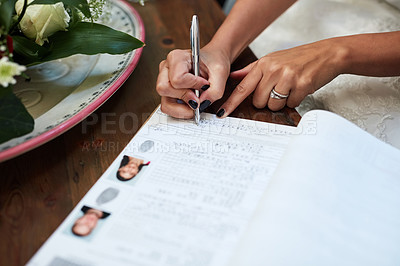 Buy stock photo Cropped shot of an unrecognisable bride signing paperwork on her wedding day