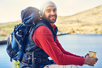 Buy stock photo Portrait of a happy hiker drinking coffee while admiring a lake view on a trail