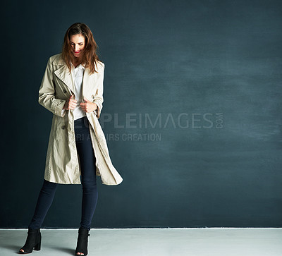 Buy stock photo Studio shot of an attractive young woman dressed in winter clothing against a dark background