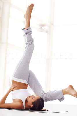Buy stock photo Portrait of fit young lady doing yoga exercise with legs raised in air
