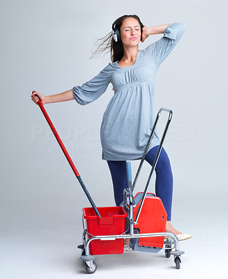 Buy stock photo Portrait of a cute young female listening to music on headphones while holding a trolley