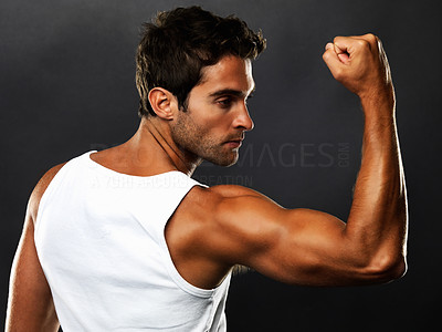 Buy stock photo Fit muscular man flexing his biceps on black background
