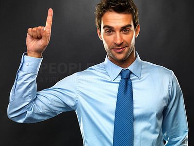 Buy stock photo Portrait of confident business man holding up his forefinger on black background