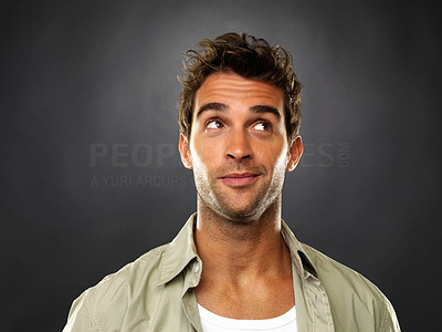 Buy stock photo Closeup of smart man looking up and smiling on black background