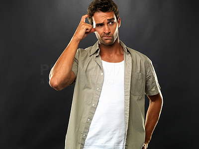 Buy stock photo Thoughtful young man standing on black background and scratching his head