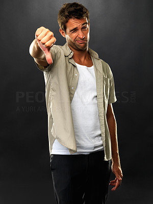 Buy stock photo Portrait of unhappy man giving you thumbs down on black background