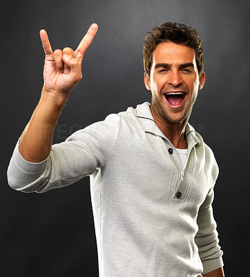 Buy stock photo Portrait of young man showing you rock sign on black background